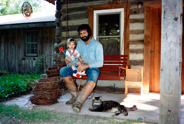 Author sitting on bench on cabin porch holding child with cat at his feet